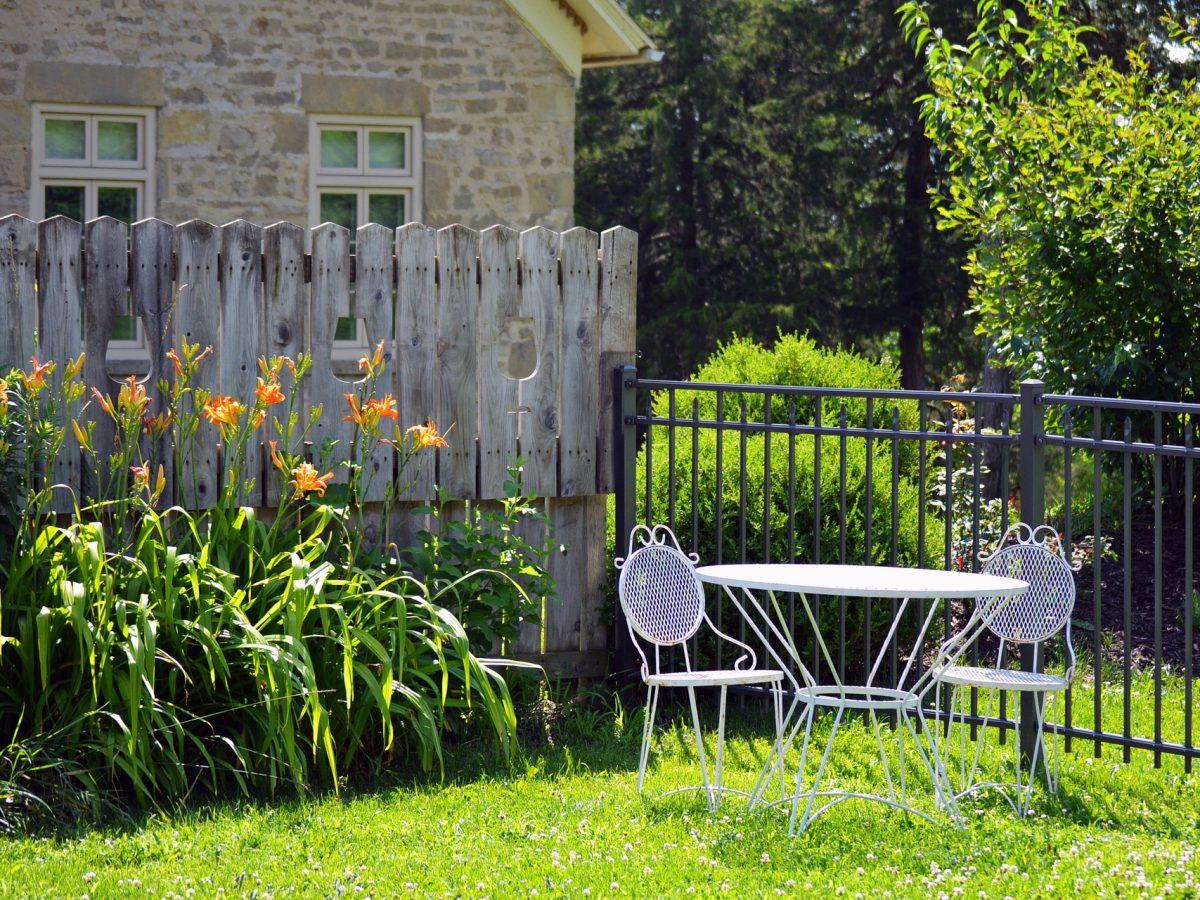 Jardin avec table et chaises et clôtures en métal et bois