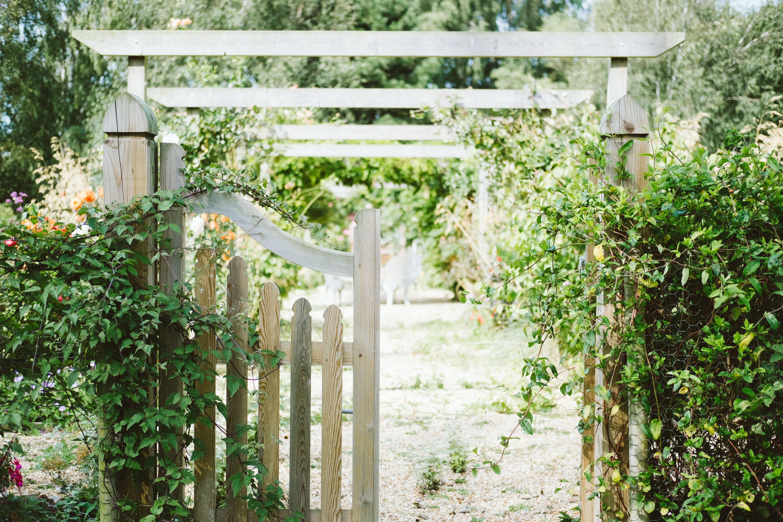 Un portail en bois ouvert qui donne sur un jardin