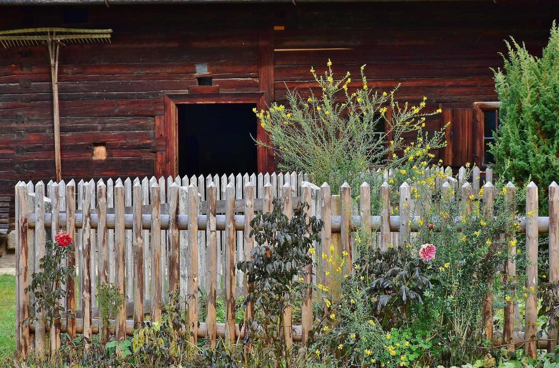 Un jardin clôturé devant une maison en bois