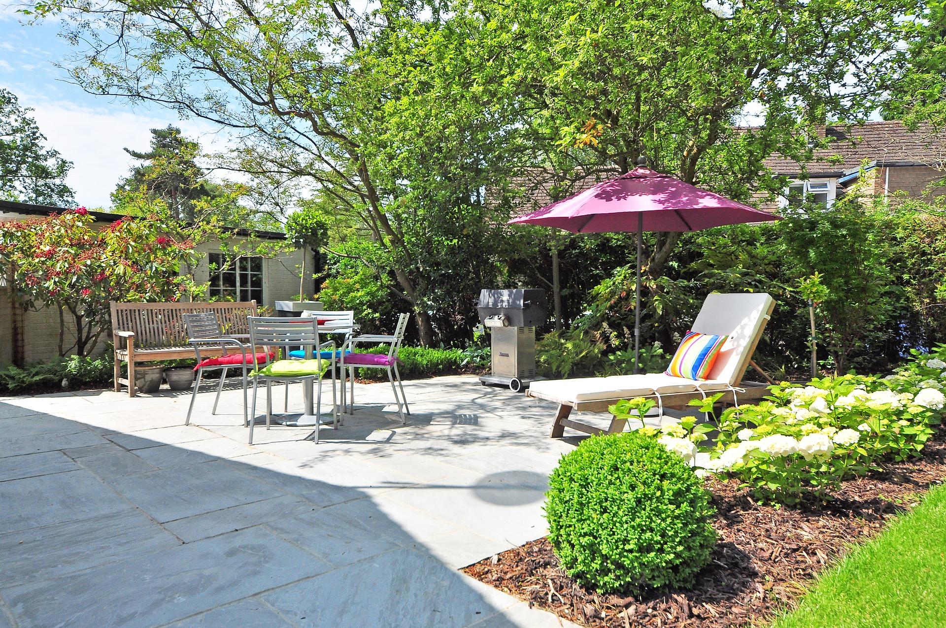 Jardin d'une maison avec une terrasse et un salon de jardin